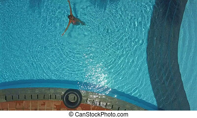 lady stands in pool and makes water circles