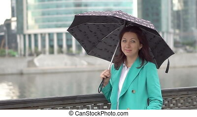 Lady stands in the rain with umbrella in hand