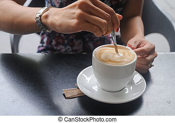 Lady stirring hot steamy cappuccino in a cafe