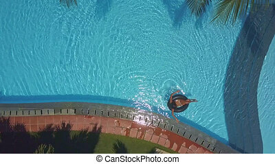 lady swims on ring by pool barrier - lady swims on...