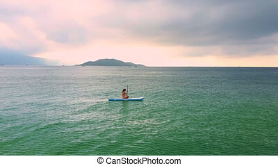 lady swims sitting on paddleboard in calm ocean at sunrise