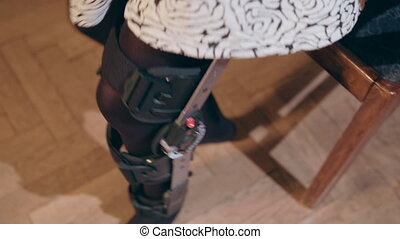 Detail of the lower half of a lady taking off a supportive leg brace. Close-up shot