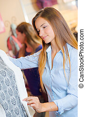 Lady touching material of jacket on a mannequin