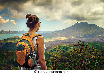 Lady tourist with a backpack standing on top of the mountain and
