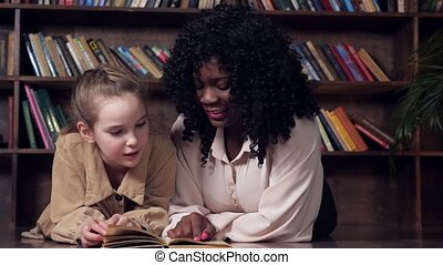 Individual black woman tutor with long curly hair teaches blonde schoolgirl sitting at table and reading book against brown wooden racks in library closeup