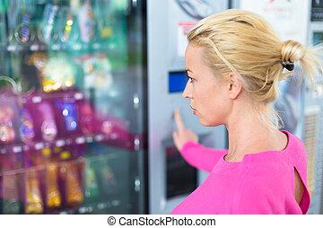 Lady using a modern vending machine - Caucasian woman...