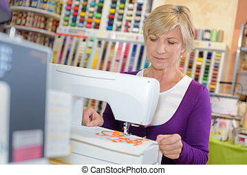 Lady using sewing machine in craft shop
