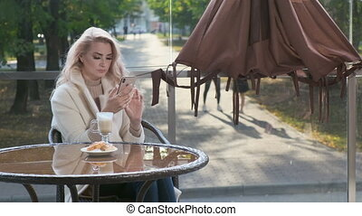 Lady using social network. On her mobile phone and drinking ...