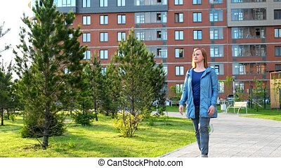 Lady walking along the courtyard - A middle-aged woman is...