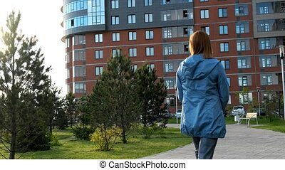 Lady walking along the courtyard - A middle-aged woman walks...