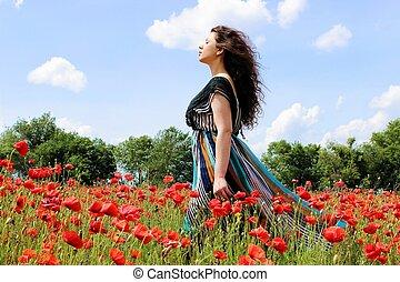 Lady walking through the poppy fiel