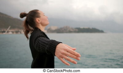 Lady with a casual hairstyle at Lake opened her arms and...