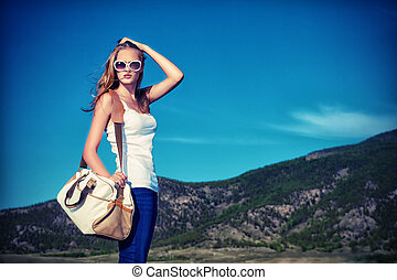 lady with bag - Beautiful young woman posing on a road over ...