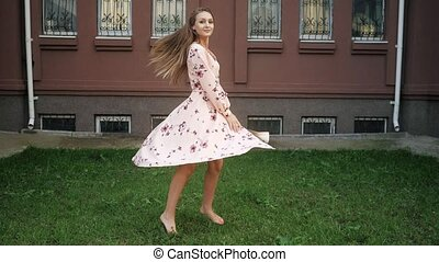 lady with fair hair in beautiful dress enjoys life and spins...