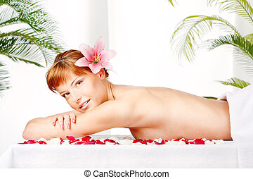 Lady with flower in hair on massage table