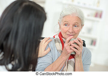 Lady with hand on shoulder of elderly woman