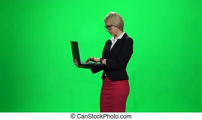 Lady with laptop in hand. Green screen