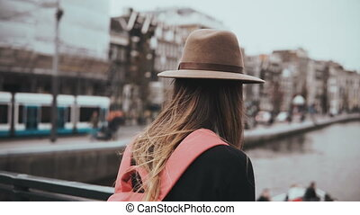 Lady with red backpack stands on river bridge. Girl in...
