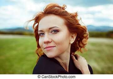 Lady with red curly hair looks stunning while wind blows along her locks