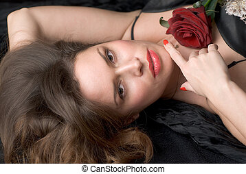 Lady with red flower against black background