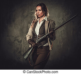 Lady with shotgun and hat from wild west on dark background....