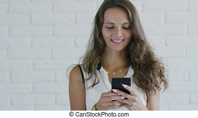 Lady with wavy hair using smartphone - Attractive young...