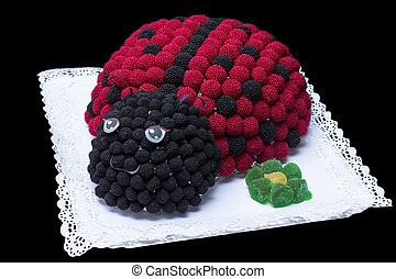 Ladybug cake made of blackberries on a black background