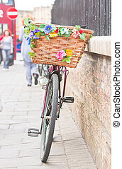 A lady's pedal bike with a colorfully decorated basket
