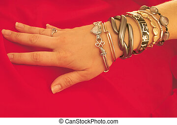A ladys hand with a spread of bracelet going up her arm.