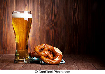 Lager beer glass and pretzel on wooden table. View with copy...