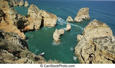 Summer holidays in Algarve, Portugal. Touristic boat trip in Ponta da Piedade and overlooks the coast of Lagos with iconic cliffs and limestone. Turquoise sea, sunny day.