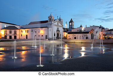 Lagos town square with fountains illuminated at dusk. Algarve Portugal.