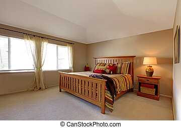 Lagre bedroom with wood bed and nightstand with stipe red, green and yellow bedding.