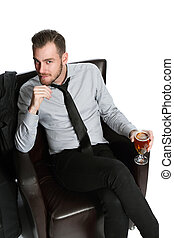 Laid back businessman with beer - A businessman sitting down...