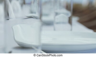 Several glasses and plates on table with a white tablecloth