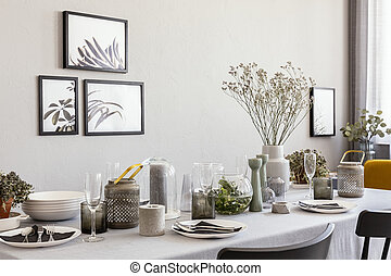 Laid table with champagne glasses and flowers in a modern dining room interior. Real photo
