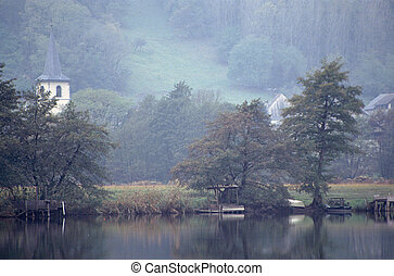 Lake and bell tower of saint helene church by a foggy day, in savoy, france