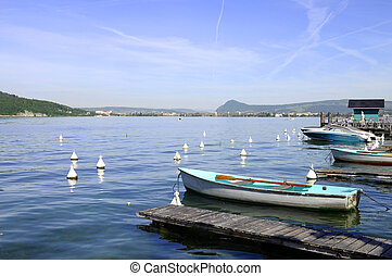 Lake Annecy and marina of Menthon, boats and city of Annecy
