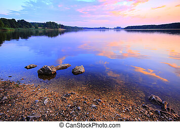 Lake at warm twilight with stony beach and fuzzy clouds ...