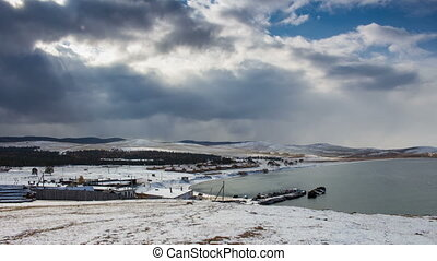 Lake Baikal landscape. Magnificent snowy scenery. Sky, clouds, water. Time lapse