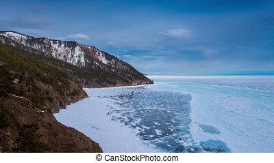 Lake Baikal landscape. Majestic winter scenery. Ice, blue sky, clouds. Timelapse