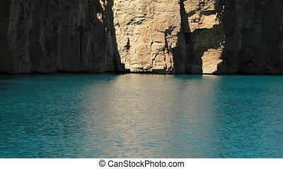 Lake basin sunlight reflecting on travertine rock walls. -...
