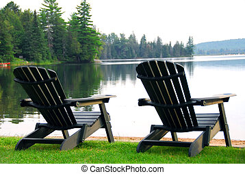 Two wooden chairs on a lake shore in the evening
