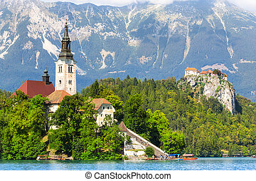 Panoramic view of Julian Alps, Bled's castle on a cliff above the lake Bled with St. Marys Church of the Assumption on the small island; Bled, Slovenia, Europe.