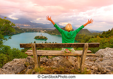 Traveler arms rised enjoying the sunset panoramic view of Julian Alps, Lake Bled with St. Marys Church of the Assumption on the small island; Bled, Slovenia, Europe.