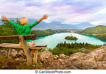 Traveler enjoying the sunset panoramic view of Julian Alps, Lake Bled with St. Marys Church of the Assumption on the small island; Bled, Slovenia, Europe.