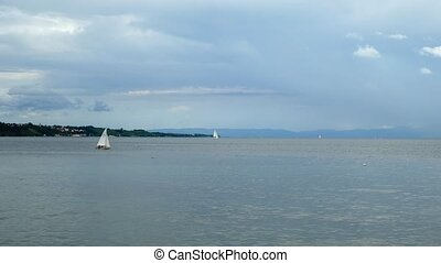 Lake Bodensee on a cloudy day where yachts swim. On the horizon you can see the port city of Meersburg.