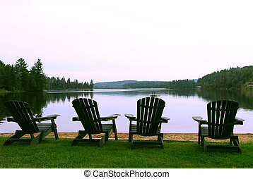 Lake chairs - Four wooden adirondack chairs on a shore of a...