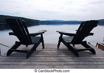 Lake chairs - Two wooden adirondack chairs on a boat dock on...