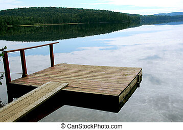 Lake dock - Old wooden boat dock on a beautiful lake in the ...